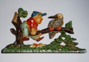 starozitna plastika kluk chlapec sedi na strome s velkym ptakem hlinik
